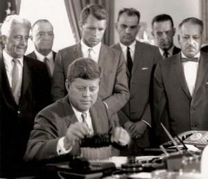 À la demande de son frère Robert, vu debout derrière lui, le président Kennedy signe trois nouveaux projets de loi anti-crime difficiles ciblant le crime organisé. Les projets de loi interdisent paris par téléphone, transport inter-États aux fins de racket et de transport commercial des équipements de paris.