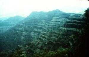 Les trapps du Deccan sont l'une des plus grandes provinces volcaniques dans le monde. Il se compose de plus de 6500 pieds (> 2000 m) de coulées de lave de basalte couchés et couvre une superficie de près de 200.000 miles carrés (500.000 kilomètres carrés) (environ la taille des États de Washington et de l'Oregon combiné) dans le centre-ouest Inde. Les estimations de la superficie initiale couverte par les coulées de lave sont aussi élevés que 600 000 miles carrés (1,5 million de kilomètres carrés). Le volume de basalte est estimé à 12 275 miles cubes (512 000 km cube) (éruption de 1980 du Mont Saint Helens produit 1 km cube de matière volcanique). Les trapps du Deccan sont des basaltes d'inondation similaires aux basaltes du fleuve Columbia du nord-ouest des États-Unis. Cette photo montre une pile épaisse de lave basaltique coule vers le nord de Mahabaleshwar. Photographie par Lazlo Keszthelyi 28 Janvier 1996.