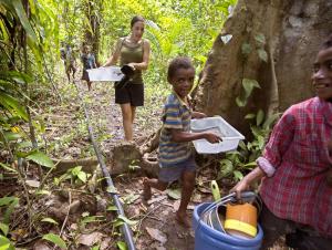 Les enfants aident biologiste Joy Smith baignoires panier en plastique de coraux et de sédiments à travers la jungle sur l'île Normanby, Papouasie-Nouvelle-Guinée. Elle cherche à savoir si le CO 2 pourrait nuire aux animaux minuscules au bas de la chaîne alimentaire marine.