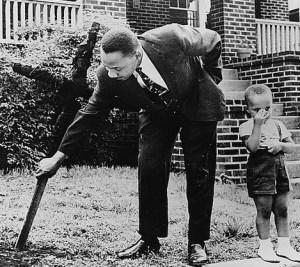 """I Have A Dream: Martin Luther King, célèbre pour son discours """"I Have A Dream"""" sur l'égalité, est montré ici enlevant une croix brûlée de sa cour avant, tandis que son jeune fils regarde ailleurs. Certaines personnes ne sont pas tellement impressionné par les droits civils et les croyances de King."""