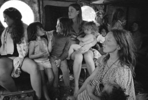 """ca. August 15-17, 1969, Near Bethel, New York, USA --- Hog Farm members ride in a bus to the free Woodstock Music and Art Fair. About 450,000 people attended the three day concert, which turned into chaos due to the crowds, heavy rains, and traffic jams. It is nonetheless romantically remembered as a symbol of the liberal spirit of the hippie generation.  The Hog Farm collective ran the free kitchen and the """"Freak-Out Tent"""" for people tripping on hallucinogens. --- Image by © Henry Diltz/CORBIS"""
