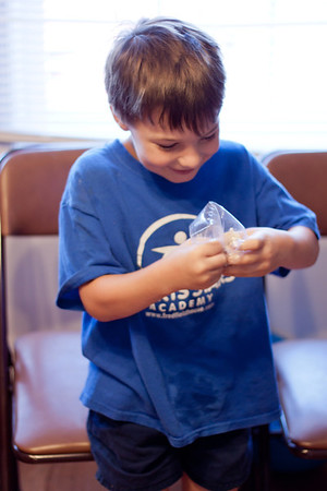 "We attended a lesson about the digestive system with our homeschool group today.  Here's Ian using his fingers like teeth to smoosh a slice of bread in a plastic bag, a model of the digestive system. We added a little water for ""saliva,"" then some soda for ""stomach juices,"" then soaked up nutrients like the small intestine with a napkin, and finally soaked up the rest of the water like the large intestine with a large amount of paper towels.  Very effective!  :)  Auto/No Flash but RAW, edited in Lightroom  I'd love to hear your critique on my editing."