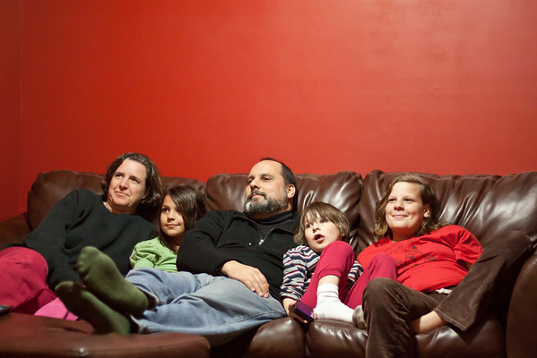 "Day 313 Family Portrait  Everyone  was watching Mythbusters except me, and they kept saying, ""Ewwwww!"" and laughing, so I went to see what they were watching.  Instead of looking at the t.v., I thought they looked so sweet lined up on the sofa that I had to go get my camera and tripod and get into the picture.  A family photo without much effort!  50mm  Manual  f/1.8  1/100sec  ISO3200  In Lightroom I decreased noise and fixed the slightly clipped shadows."