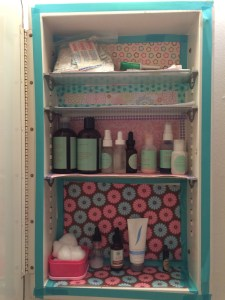 Bathroom shelves decorated with scrapbook paper and washi tape.