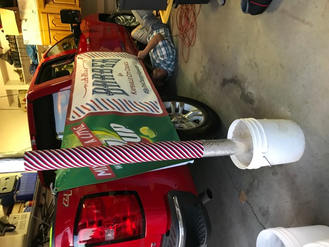 Husband adding donated signs and Barber Poles and banners hand crafted by my mom and sister.