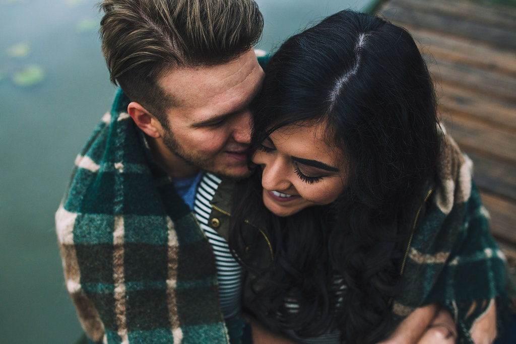 A lake engagement photo of a couple leaning in close, wrapped in a blanket, on a dock