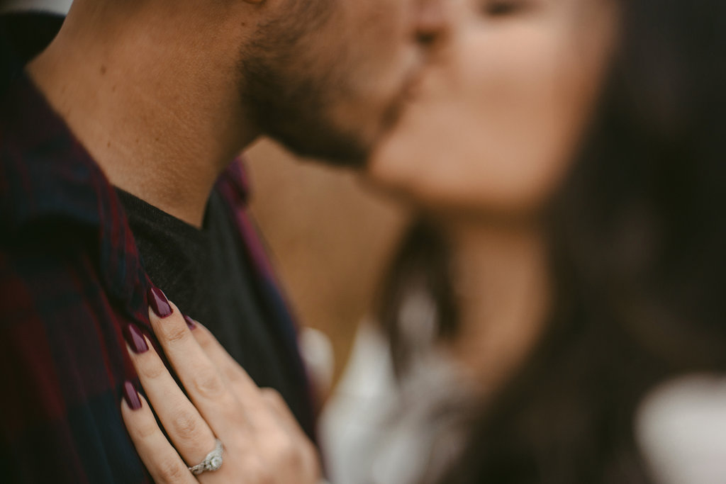 A couple kissing with the focus on the engagement ring in this free-lensed fall engagement photo.