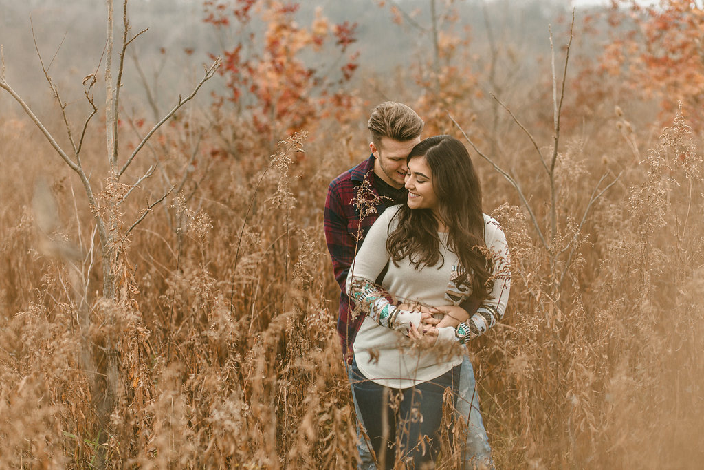 A couple standing in a golden field in a fall engagement photo session.