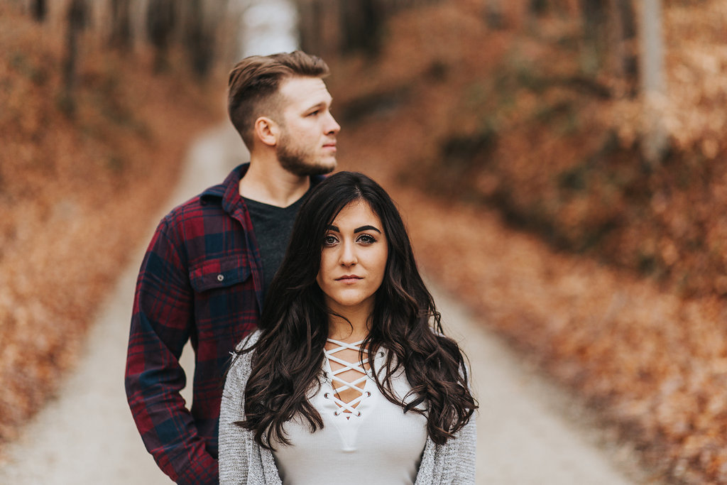 Autumn Engagement Photo of a couple standing on a path surrounded by fallen leaves in Bloomington, Indiana