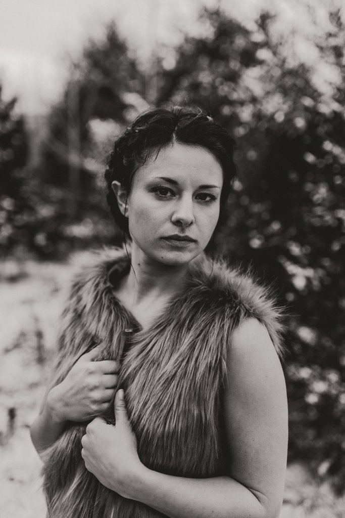 A close-up winter black & white portrait of a woman clutching her Fur Vest tightly against a snowy forest background.