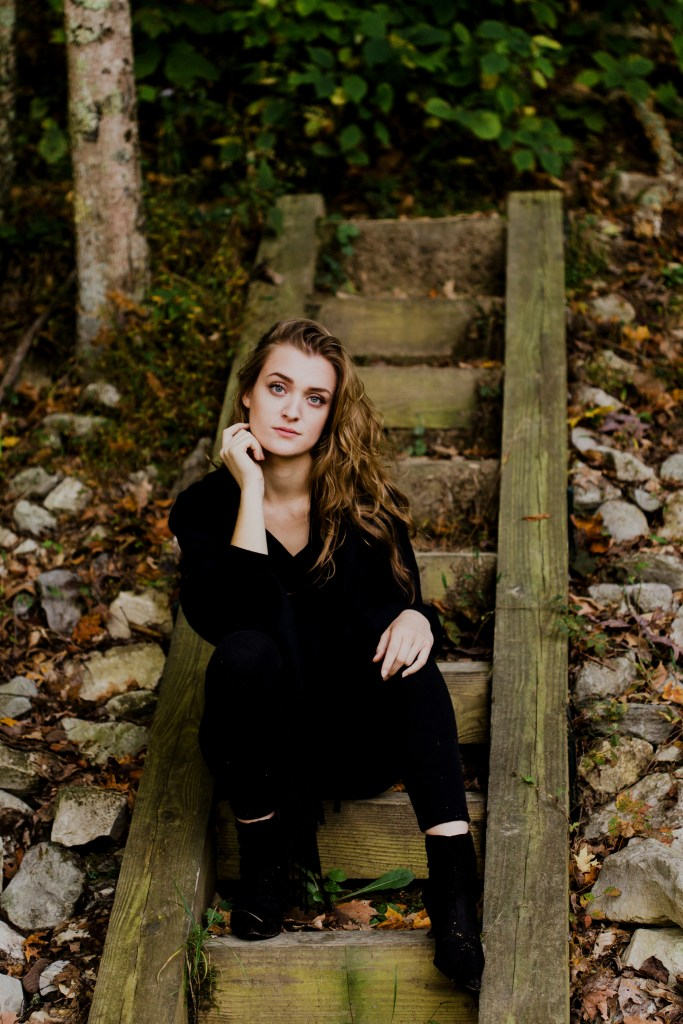 A portrait of Hanna sitting on wood steps in the Morgan-Monroe State Forest.
