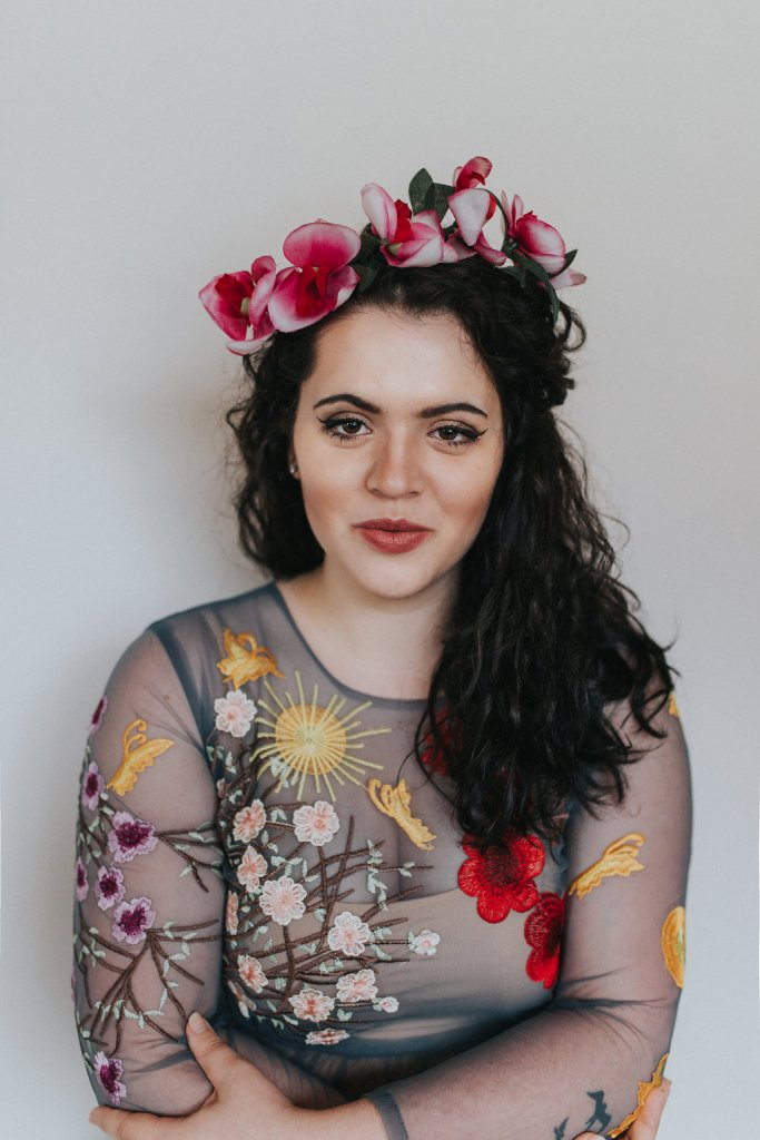 A photo of a girl wearing a flower crown made of orchids. The girl is wearing a blue dress with florals embroidered all over the entire thing.