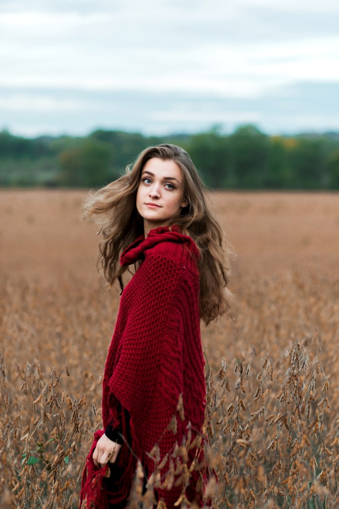 Hanna | A girl in a red cape spins in a golden field. Her blonde hair mimics the movement of her cape.