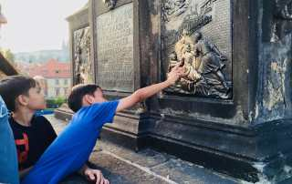 Touch the St John Statue on the Charles Bridge in Prague for good luck