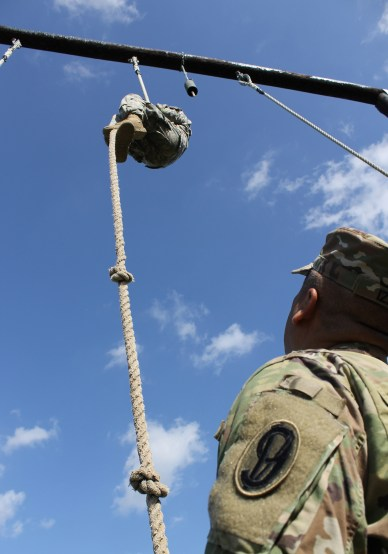 Army Reserve Staff Sgt. Jonathan Davis with the 104th Training Division (LT) reaches the top of the rope obstacle while a 95th Training Division (Initial Entry Training) safety noncommissioned officer looks on during the 2017 108th Training Command (IET) Best Warrior Competition at Camp Bullis, Texas, March 19-24, 2017. (U.S. Army Reserve photo by Maj. Michelle Lunato.)