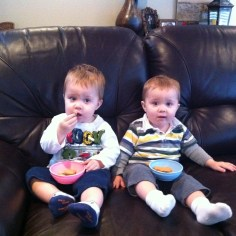 The boys sitting on the couch just before they turned 1