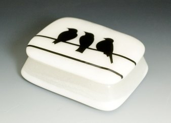 Birds on a wire in black, on a white/clear cast glass box