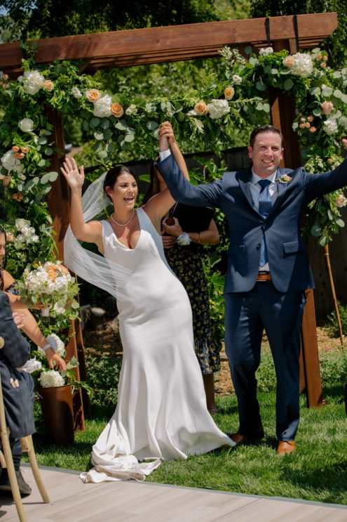 bride and groom celebrate at their backyard wedding