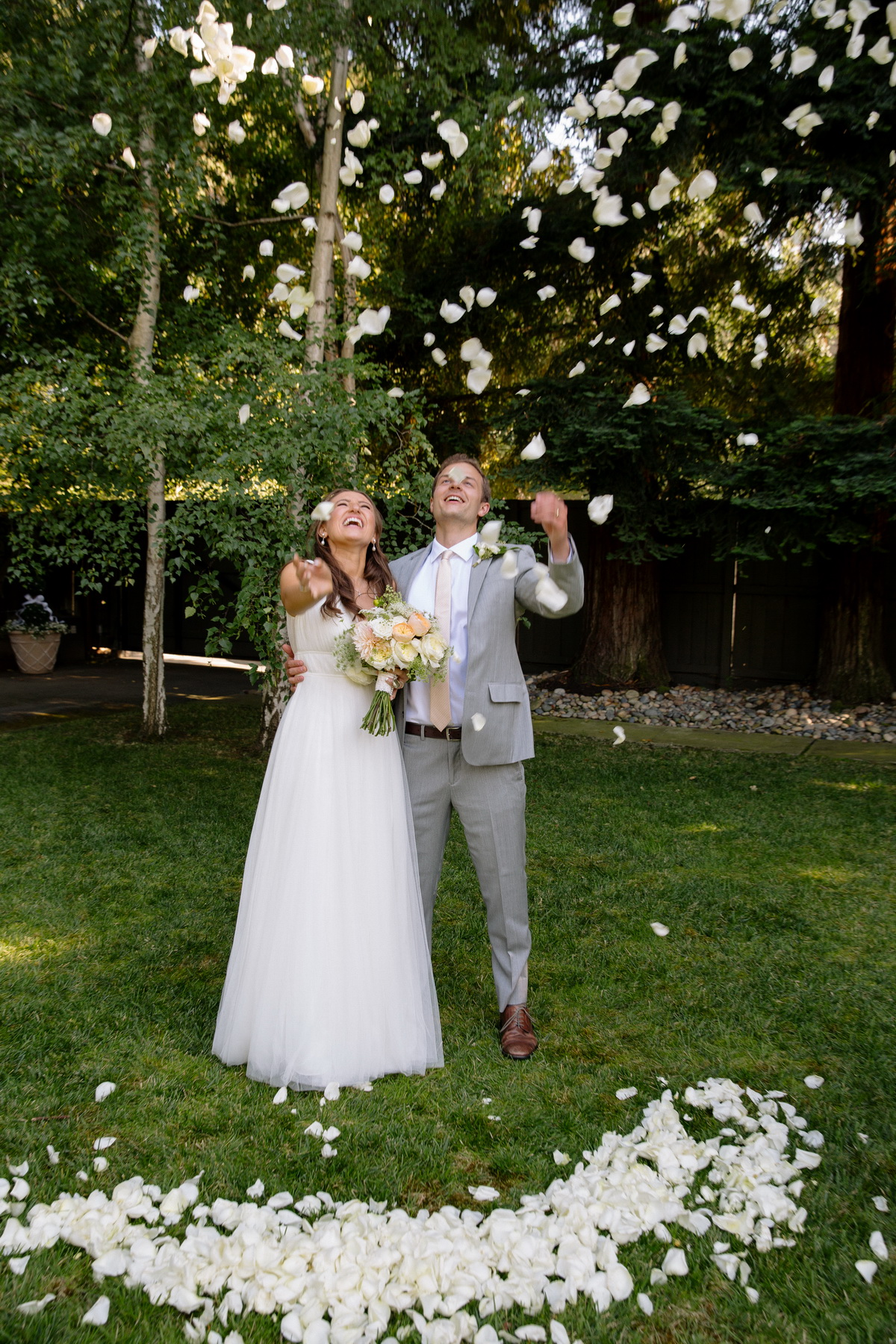 couple throwing flowers at their backyard wedding