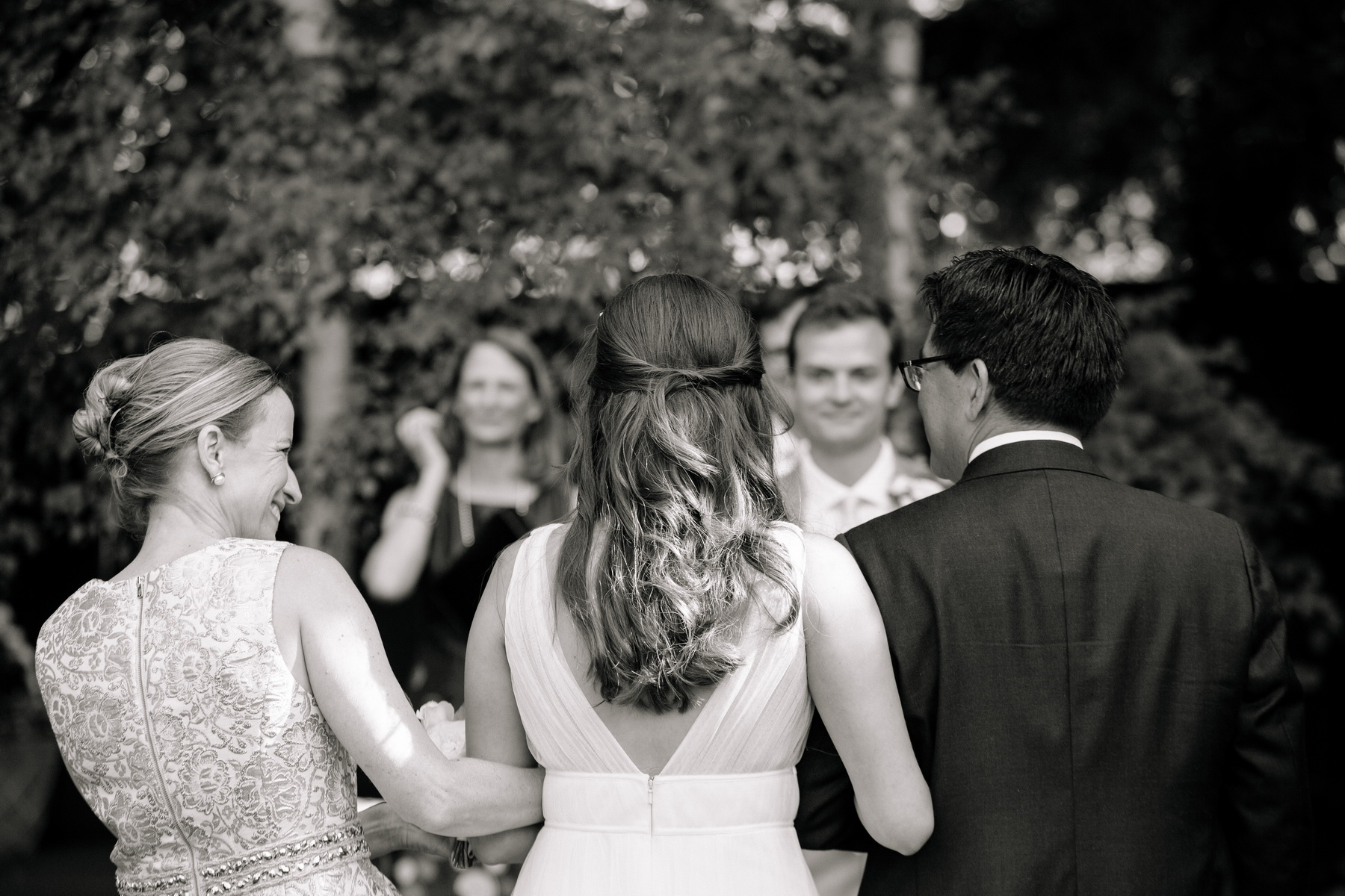 bride sees groom for the first time walking down the aisle at her backyard wedding