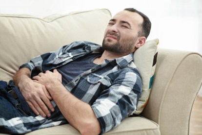 Man with Inguinal Hernia in pain on couch