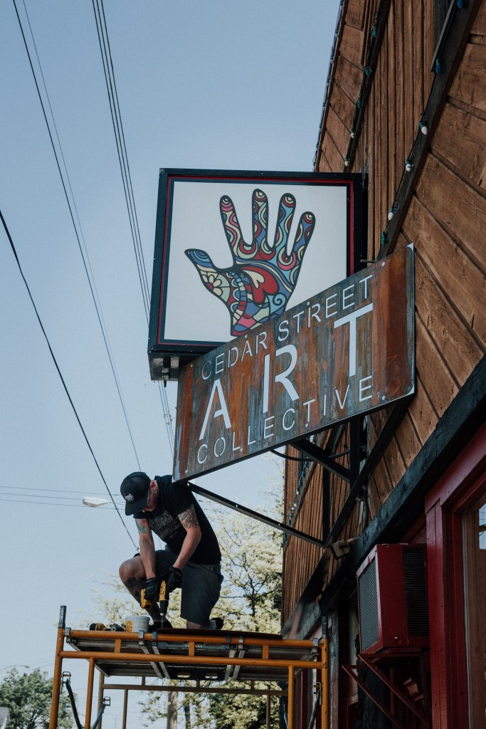 Custom steel sign being installed by Dane Vermeulen at Michigan Imagery in Lansing.