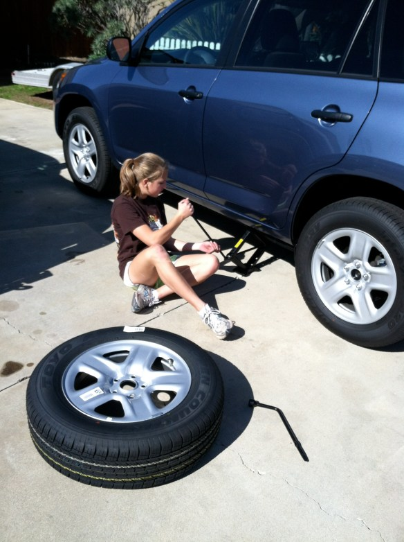 Daughter Tori practices changing a modern tire.