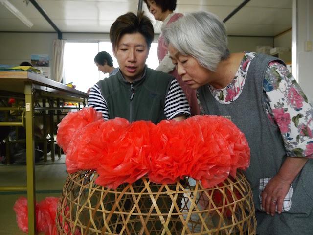 仮設のお母さんに、飾りづくりを教える近江さん
