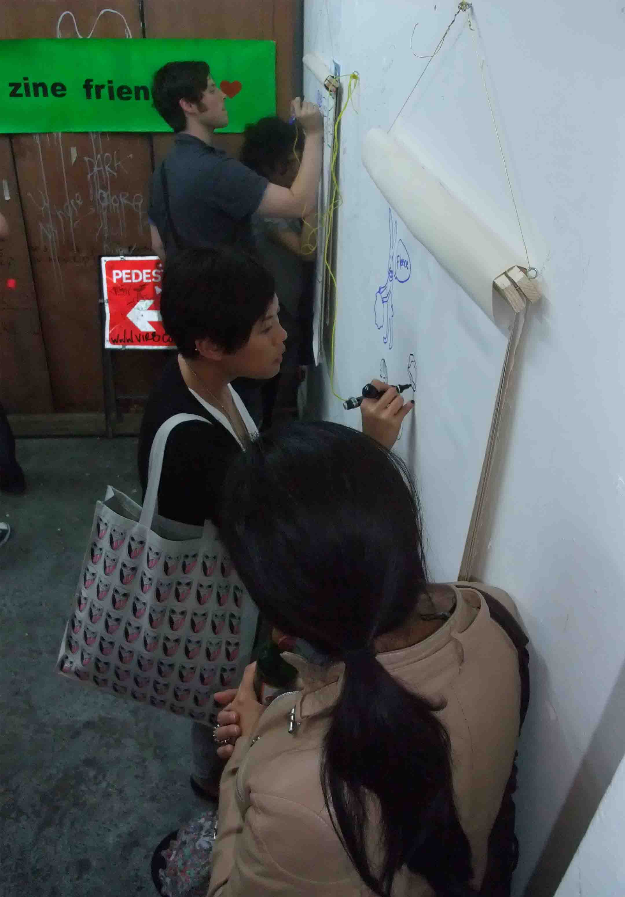 Passersby draw on the zine wall...