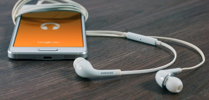 a photo of a white phone on a brown table. The phone has white ear bud ear phones plugged into it and also sat beside it on the table. The phone has an orange image on the screen.