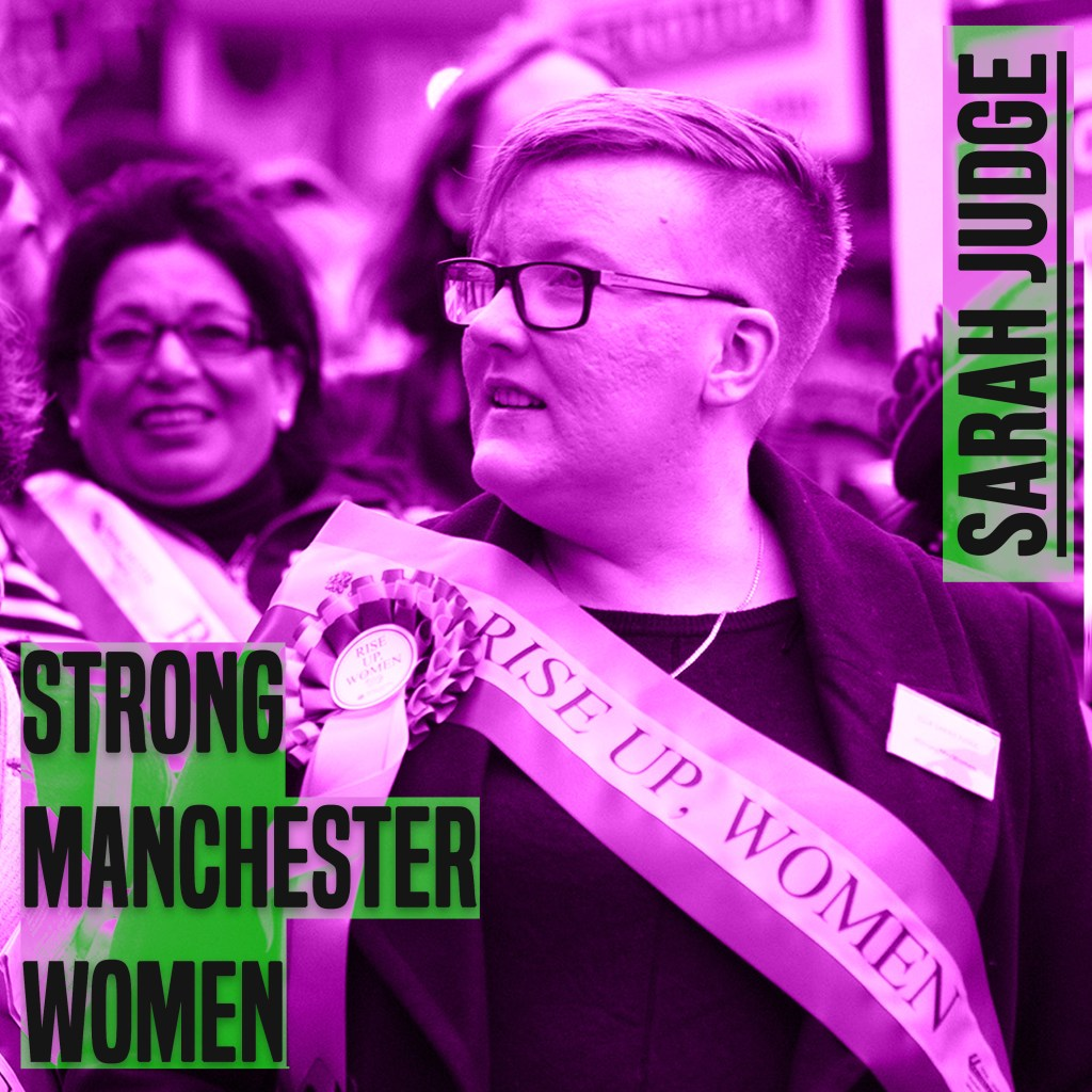 The picture is a of a woman from chest height up. She has her head turned to the left. She has short hair and glasses. she is wearing a sash. She The picture has a purple hue to it. On the leff of the picture are the words 'strong manchester women' on the right 'Sarah Judge' - both in capital and grey colour letters