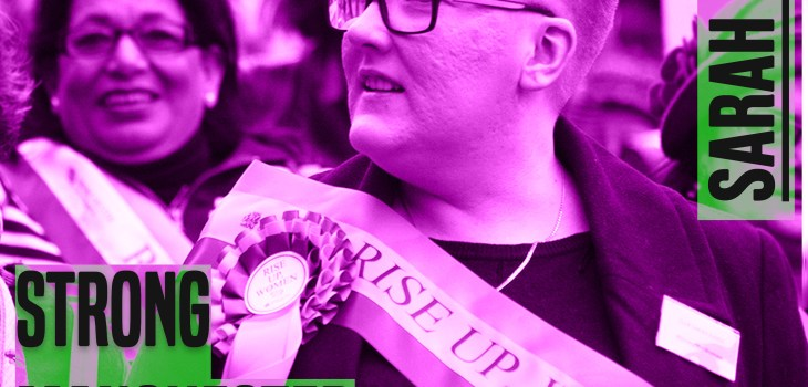 The picture is a of a woman from chest height up. She has her head turned to the left. She has short hair and glasses. she is wearing a sash. The picture has a purple hue to it. On the leff of the picture are the words 'strong manchester women' on the right 'Sarah Judge' - both in capital and grey colour letters