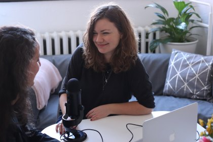 a an image of twowomen talking with microphone between them