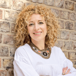 a woman leans against a wall with her arms crossed. she is wearing a white top and is smiling with blonde curly hair