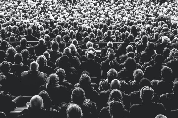 [Image of heads sat down in a crowd]