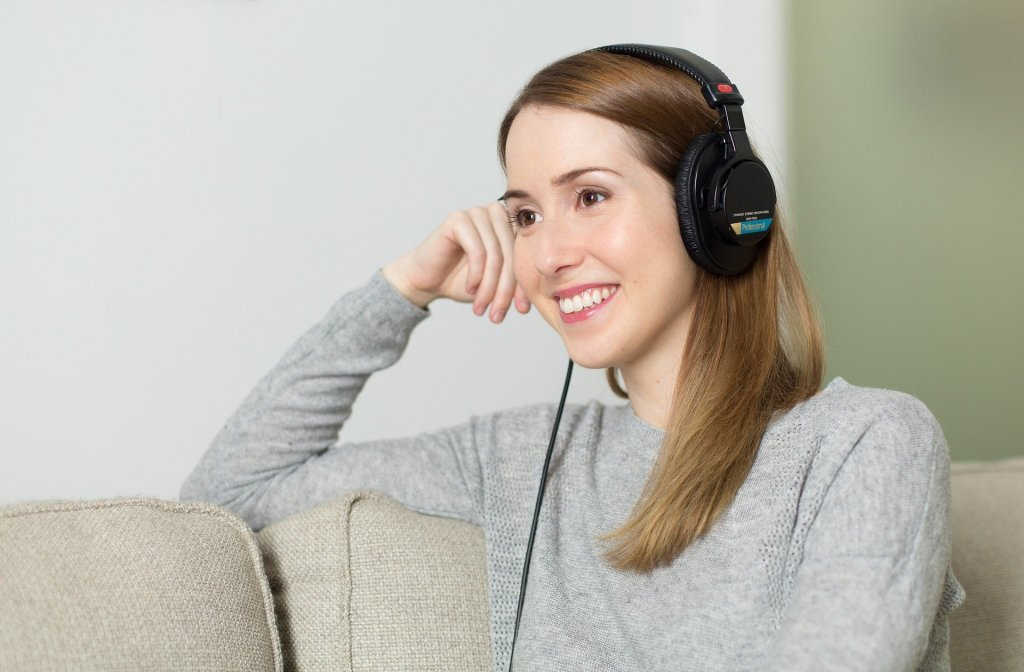 [Image of a lady in a grey jumper with brown hair smiling with headphones on]
