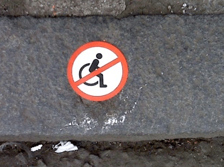 Calling attention to inaccessible pavements. Truth telling street signs.