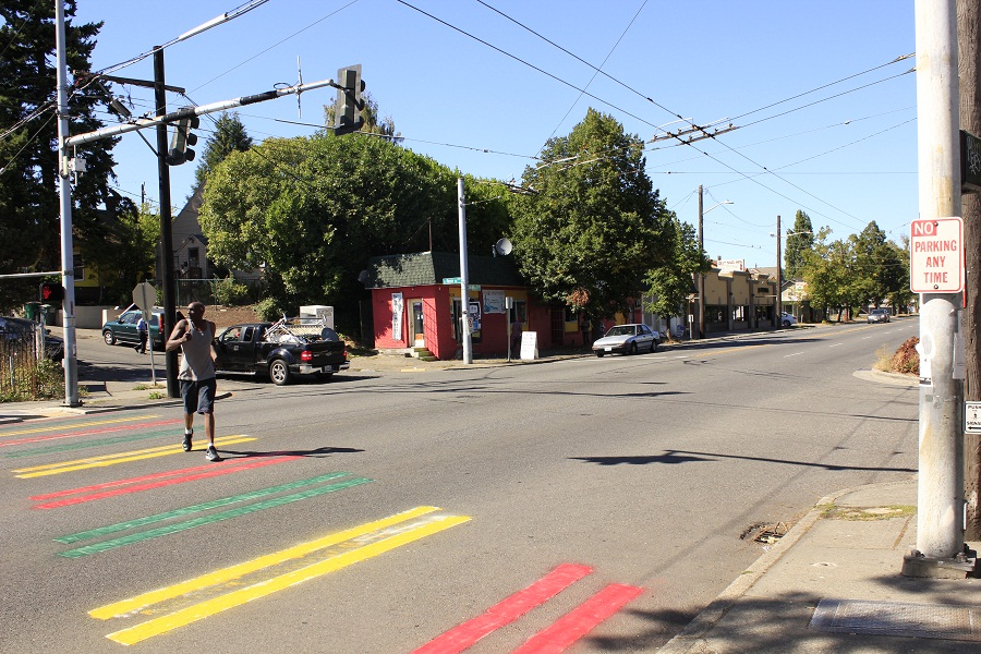 """Rainier Beach crosswalk painted Ethiopian colors. """"According to a notes posted nearby, the aim was to raise concerns about gun violence, gentrification and incarceration."""""""