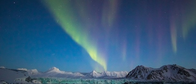 Arctic winter in south Spitsbergen. Aurora borealis over the glacier.
