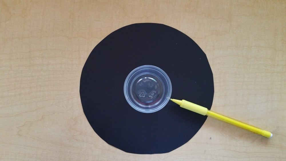 Tracing another circle into the center of the paper circle.