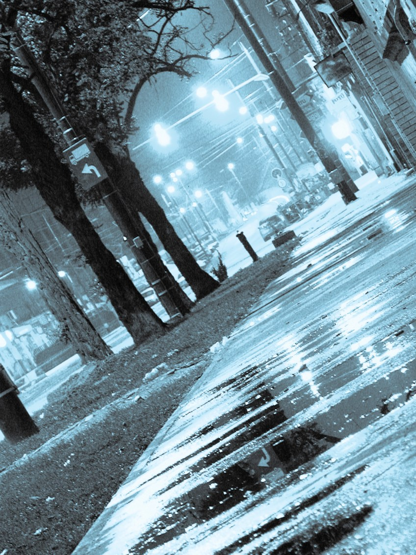Cyan-colored city scene, at a dutch angle, shortly after it rained