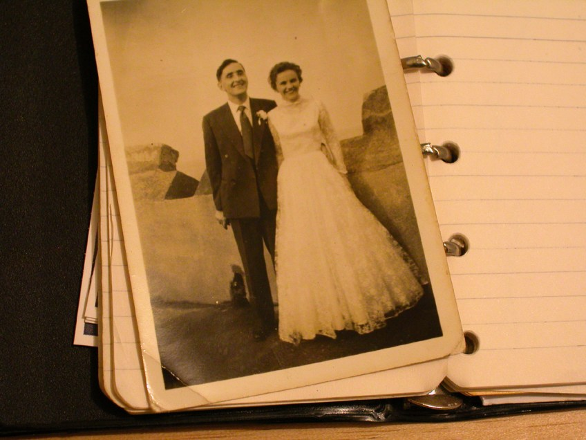 older photo of bride and groom in photo album