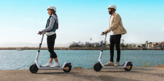 Two people riding Bird Scooters on the waterfront