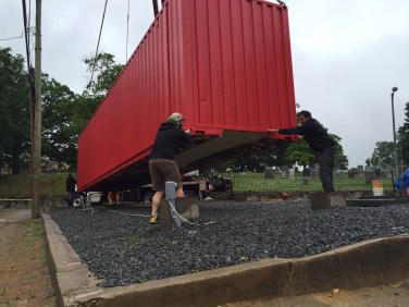 Brian, Mark and two friends aligning shipping container to site