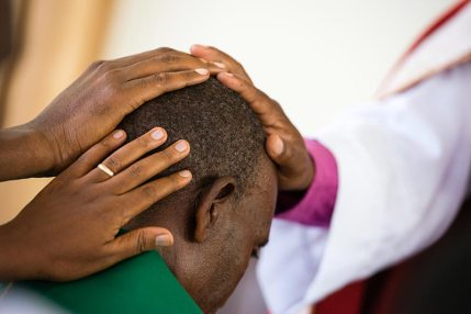 laying-hands-on-pastor Mission trip in Tanzania