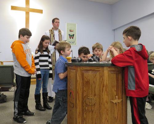 Dedication day with children praying around the font, Praise Lutheran Church in Maryville, TN