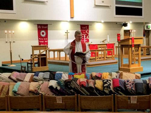 Emmanuel Lutheran pastor blesses quilts for Care-Van 2019