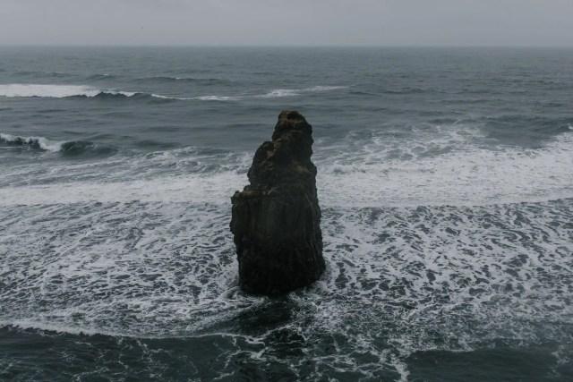 rough rock in foamy shallow sea
