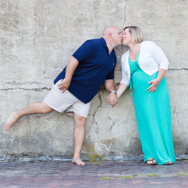 Maternity Photography - Older Couple kissing in front of grey brick wall