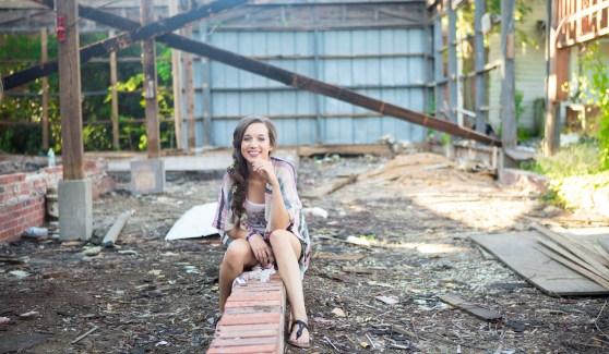Senior Photography - Senior girl sitting on bricks in abandoned building